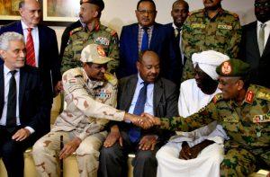 I partecipanti all'accordo chiave per terminare il conflitto in Sudan si stringono la mano. Da sinistra l'inviato in Sudan dell'Unione Africana Hebatt, il generale Dagalo, il diplomatico etiope Mahmud Dirir, il leader dei comunisti sudanesi Siddig Yousef e il generale Yasser al-Atta (Credits: Ebrahim Hamid/Agence France-Presse-Getty Images)